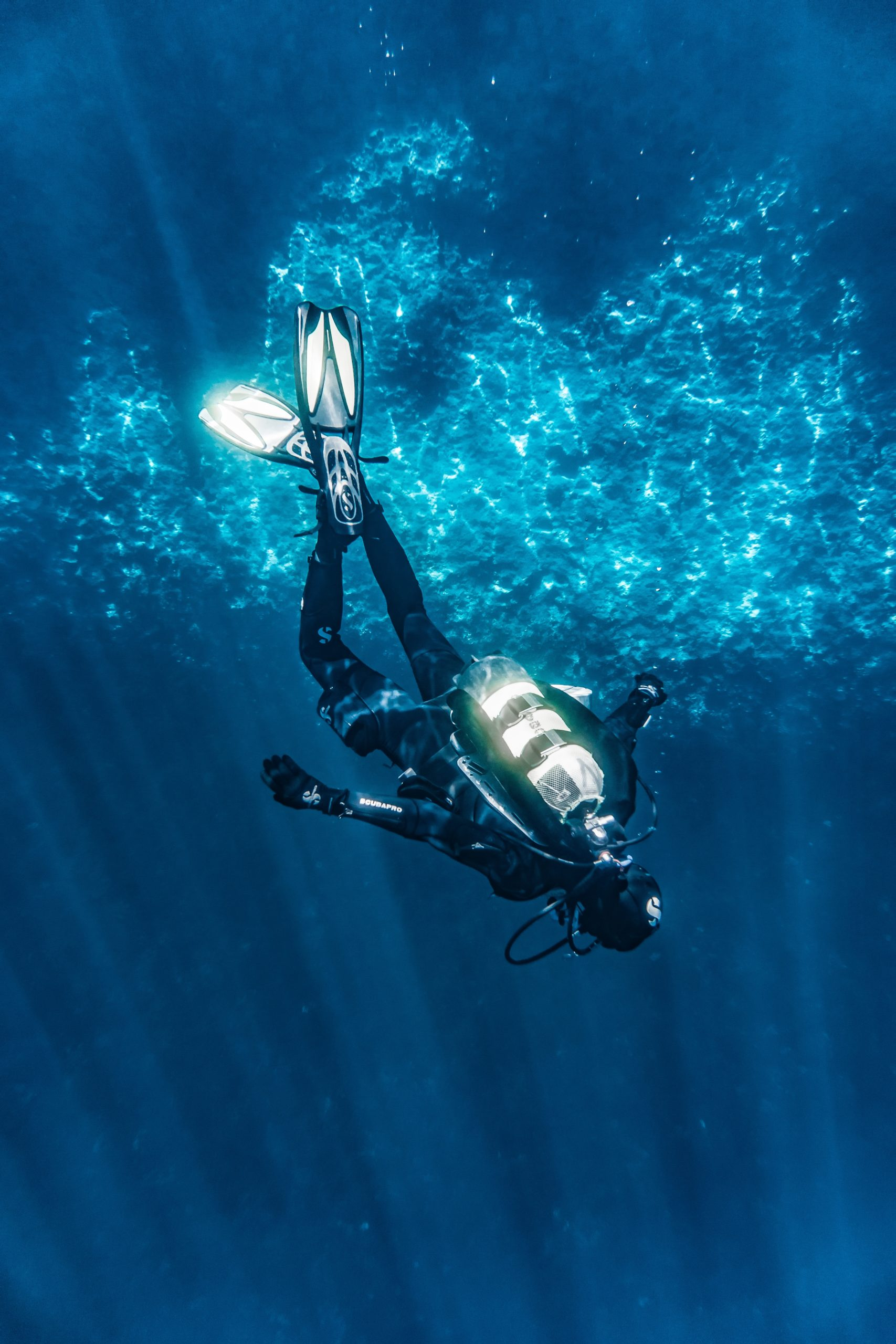 how do scuba divers go up and down safely? This diver is descending head first.