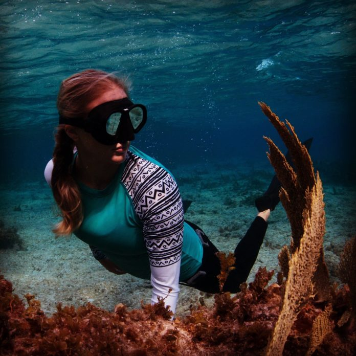 Britney Ouellette freediving with coral underwater