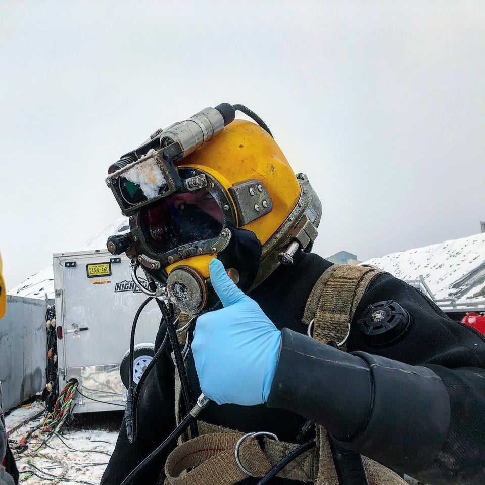 A commercial diver giving the thumbs up. He is wearing his full equipment.