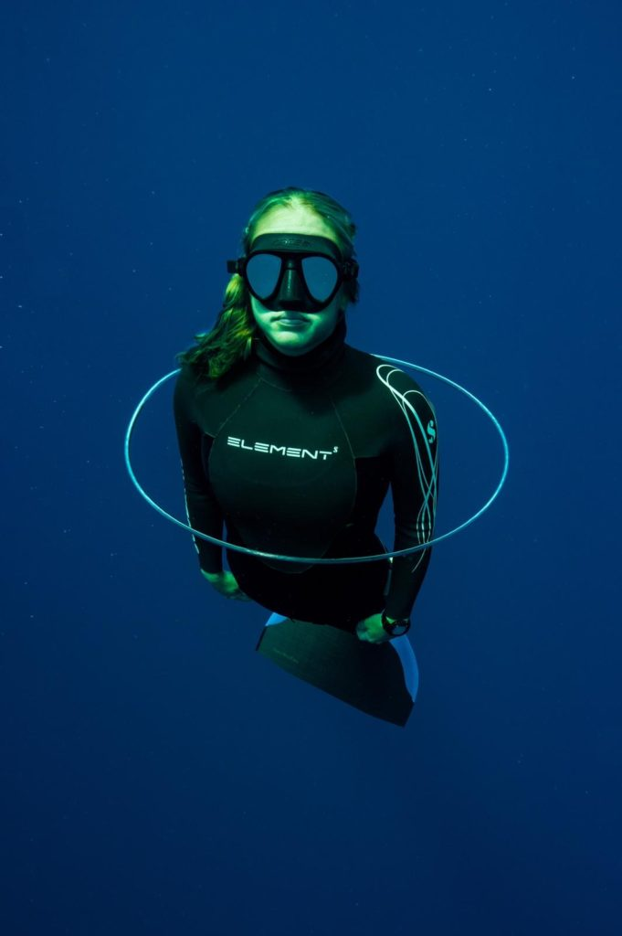Freediver underwater swimming through a bubble