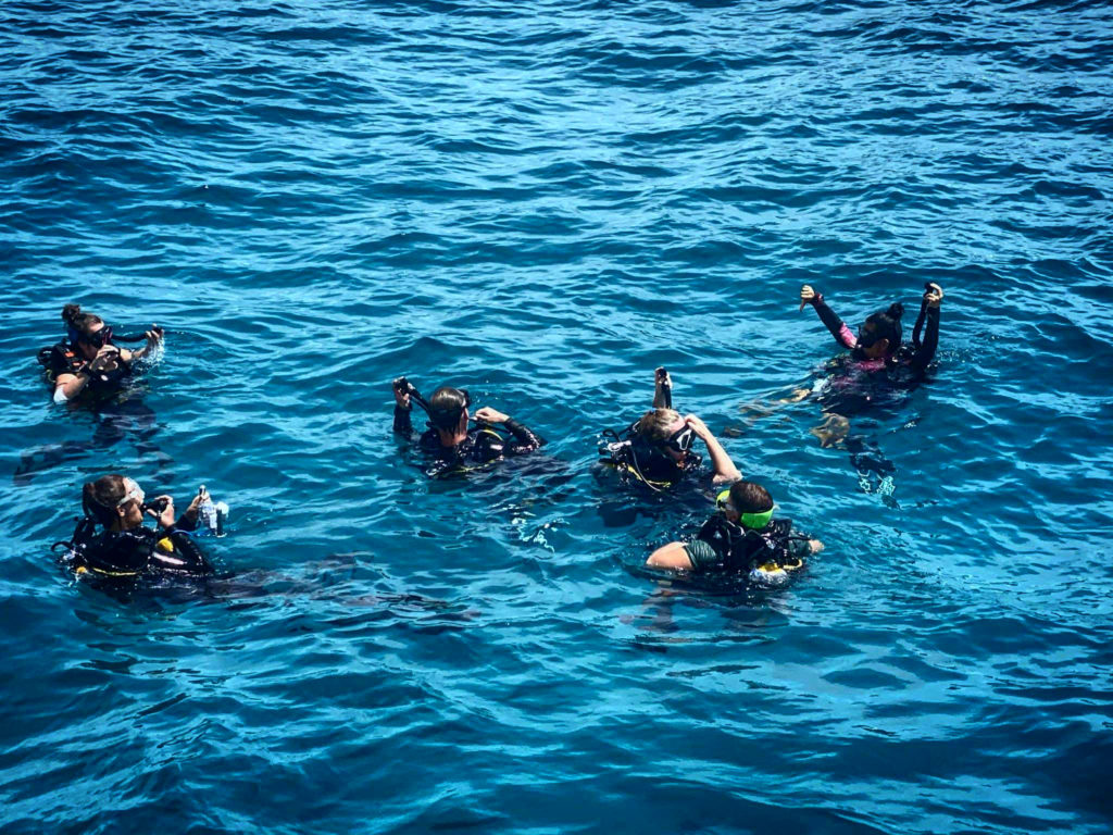 PADI instructor Emma Ong descending with a group of scuba divers