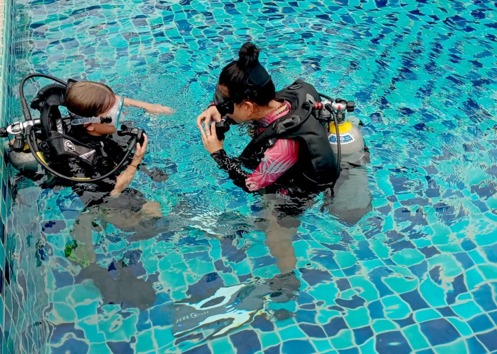 Instructor Emma teaching scuba diving to a child in the swimming pool
