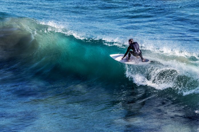 A man wearing a wetsuit is surfing. We want to know what are the differences; diving wetsuit vs surfing wetsuit?