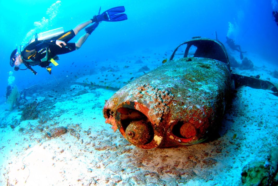 a scuba diver next to a car wreck. We want to know how long does a scuba certification last if you don't dive often.