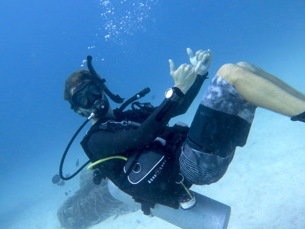A scuba instructor showing us what scuba diving is underwater.
