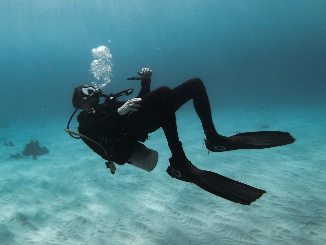 A man wearing a wetsuit is upside down as he contemplates how much does a wetsuit cost?