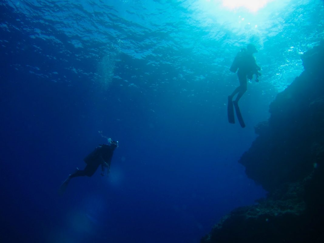 Scuba divers in the blue. We look at the different types of scuba certification levels for beginners, advanced and professional levels.