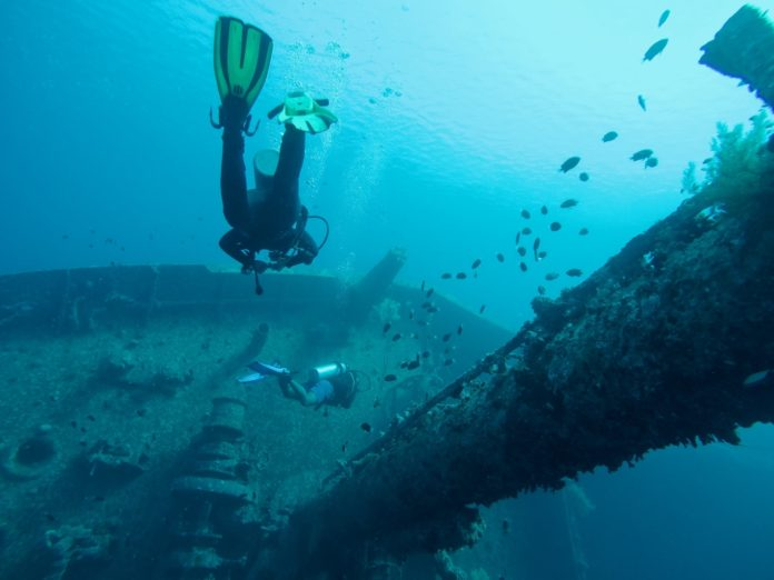 Scuba divers diving on a wreck. It is important to know how to give a good briefing before every dive.