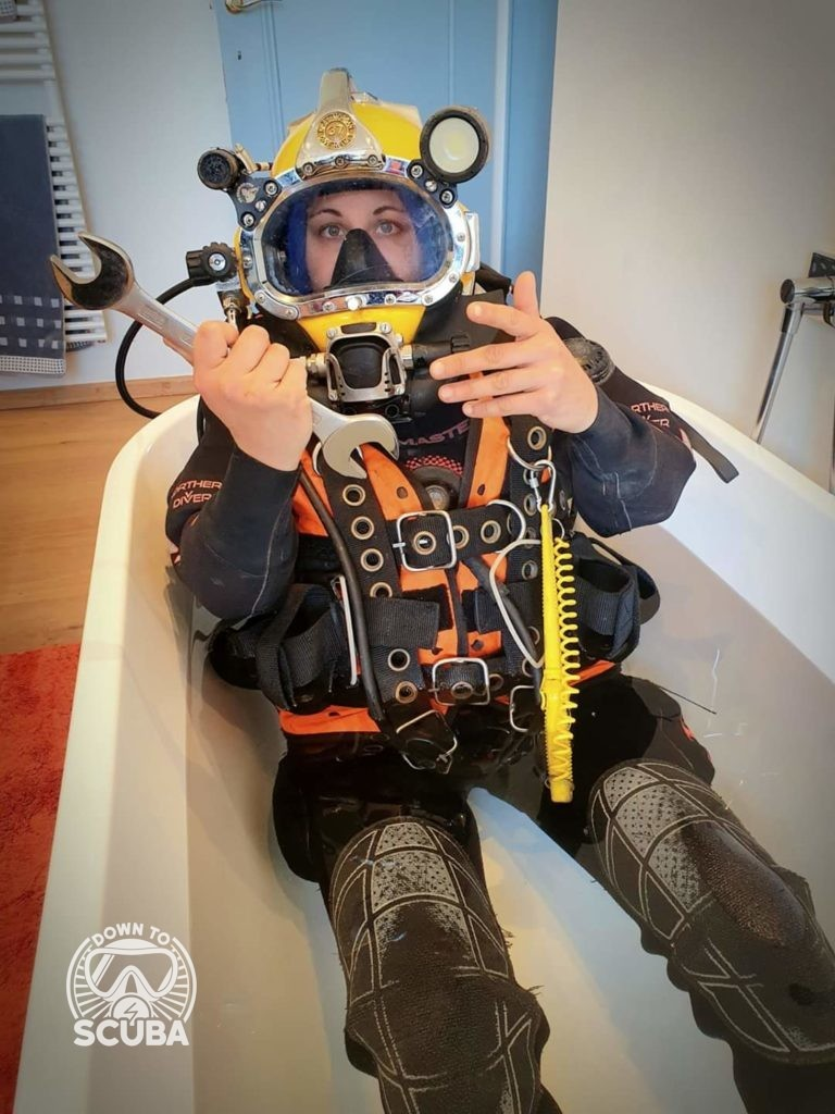 Marie, a female commercial diver in her suit with a wrench in the bathtub