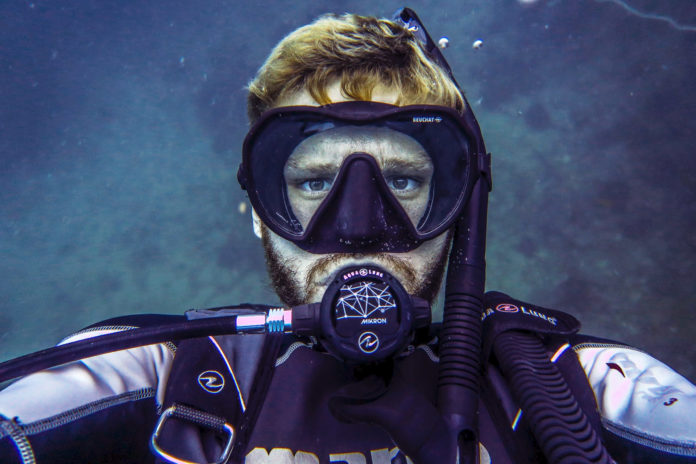 A diver taking a selfie underwater. We want to know mask clearing tips to use underwater.