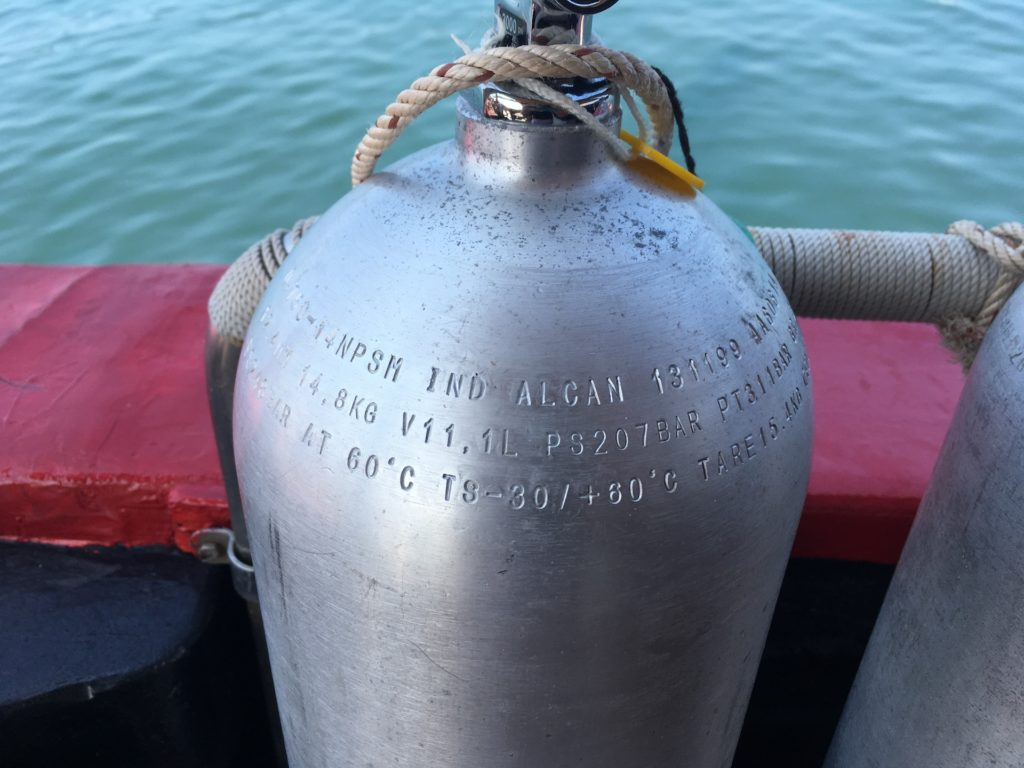 A scuba tank with markings on it. This shows the hydrostatic test date and size of the tank.