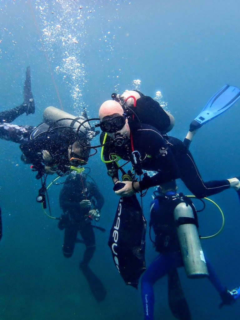 Divers Underwater Collecting Rubbish