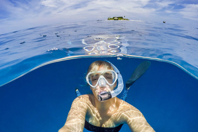 How To Snorkel: Girl snorkeling in front of tropical island.
