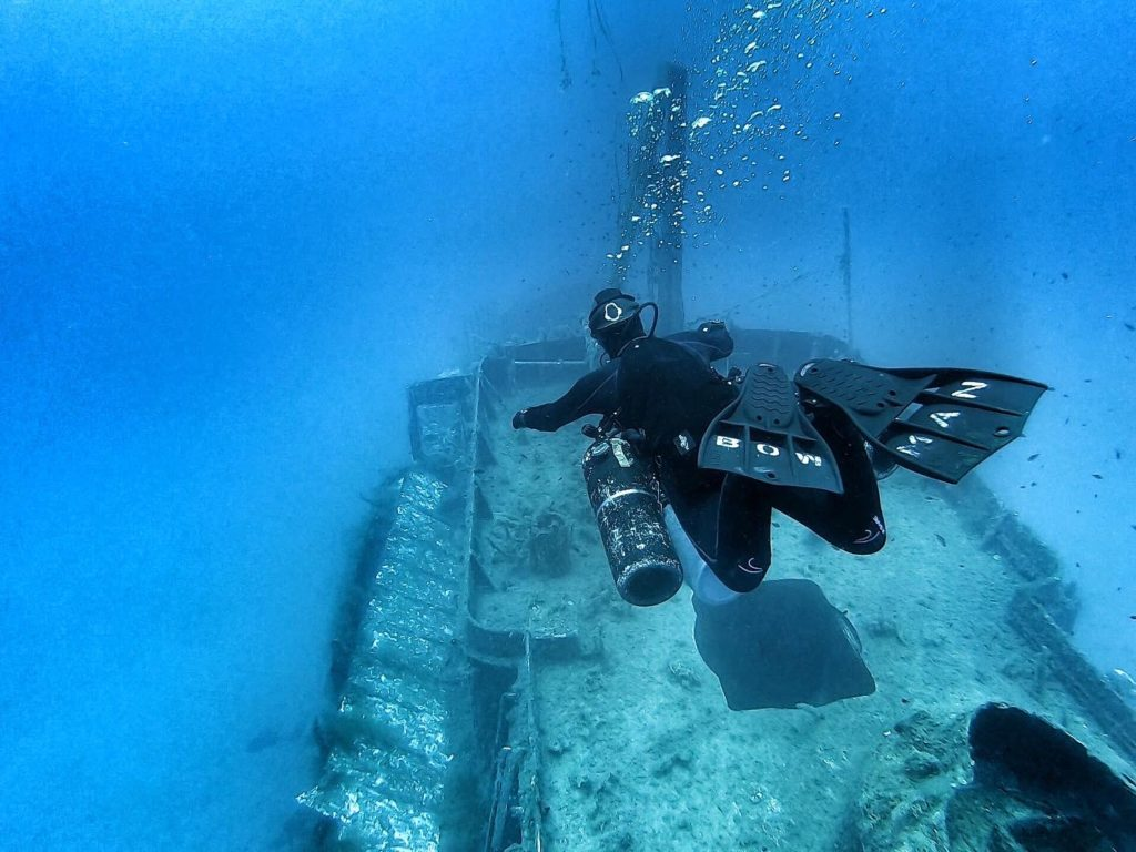 Female tech diver descending onto a wreck