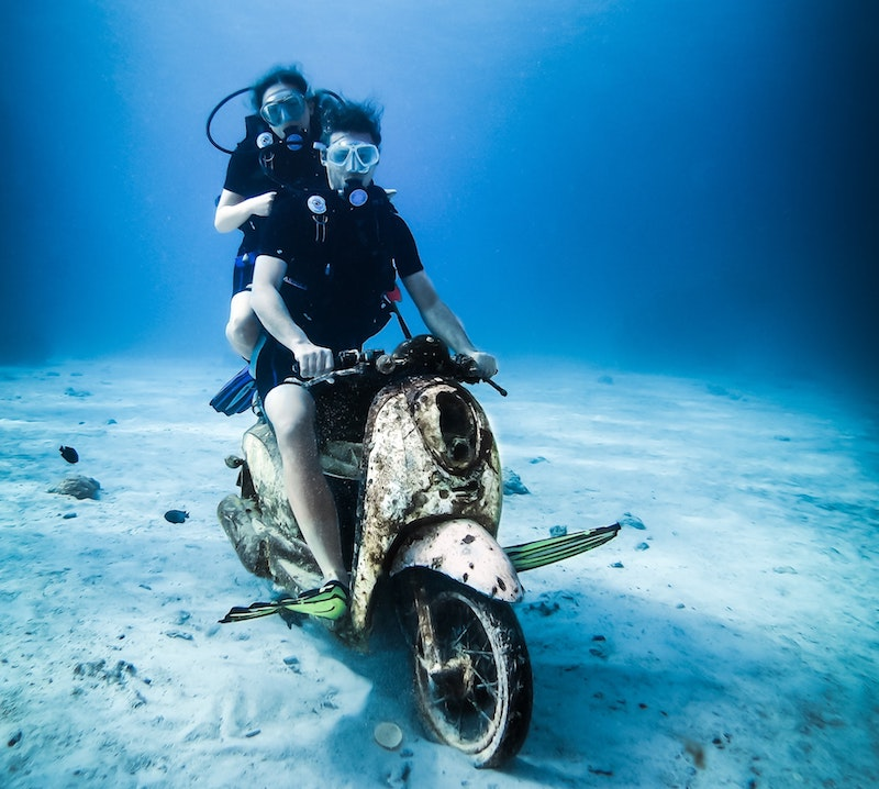 Two scuba divers riding an underwater scooter